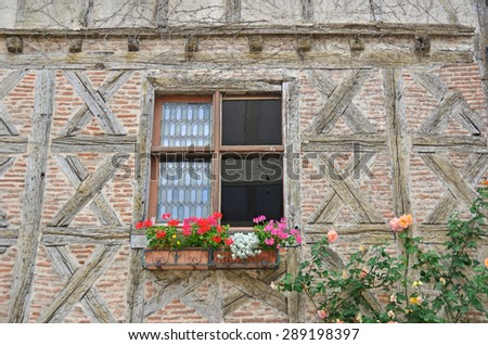 A traditional half timbered house with simple saltires and brick filling , decorated with climbing roses and geraniums - stock photo