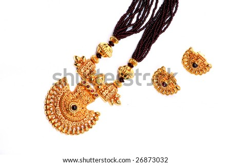 A traditional Indian ethnic jewelery set consisting of a gold design necklace & earrings, on a white fabric. - stock photo