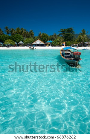 A traditional longtail boat floats in perfect crystal clear water on the island paradise of Ko Lipe, Thailand - stock photo