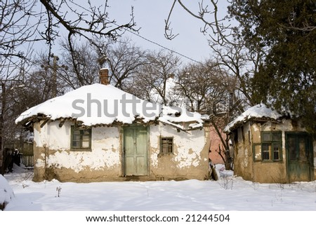 a traditional mud built farmhouse in winter - stock photo
