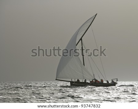 A traditional racing dhow in the Arabian Gulf moonlight off Dubai. - stock photo