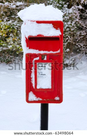 A traditional red English postbox at winter time covered in snow. - stock photo