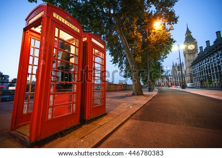 A traditional red phone booth in London with the Big Ben in the background - stock photo