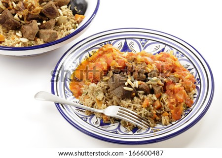 A traditional Saudi Arabian or Gulf Arab meat kabsa meal, of rice, onion, carrots, capsicum, spices, and beef, served with a homemade tomato sauce topping. This  is also known as majbus or machboos - stock photo