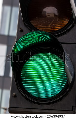 a traffic light is green light for unlimited travel through the intersection - stock photo