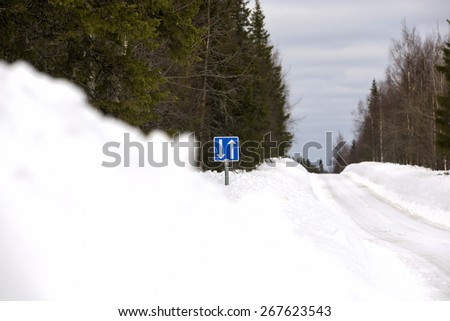 A traffic sign telling that there is a place to dodge another car. Traffic sign is in the deep snow. - stock photo