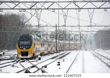 A train is arriving on a snow covered train station in the winter - stock photo