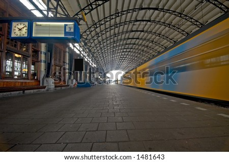 A train station in the netherlands with train in motion - stock photo