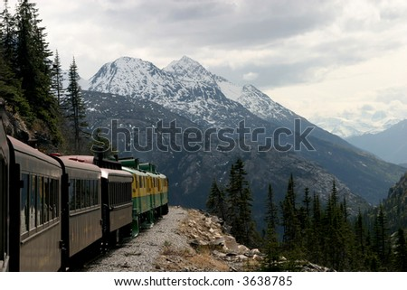 A train takes tourists through the Canadian Rockies and Alaska. - stock photo