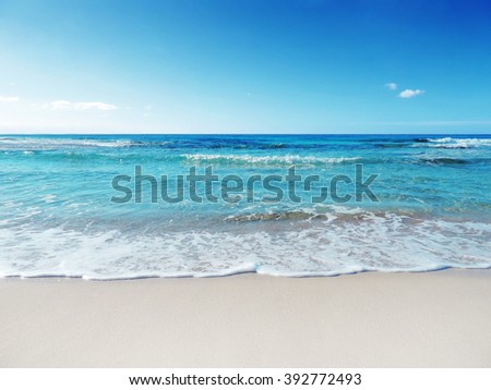 A tranquil sun and sea scene. The gently rolling waves of the sea roll in and out. The shot is taken on the white sands of a tropical beach. The water is a crystal-blue color. - stock photo