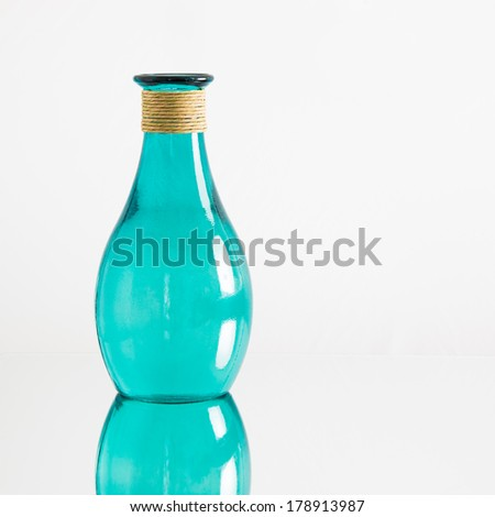 A transparent blue-green glass vase or bottle, with reflection, on white background - stock photo