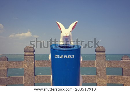 A trash bin with a rabbit. - stock photo