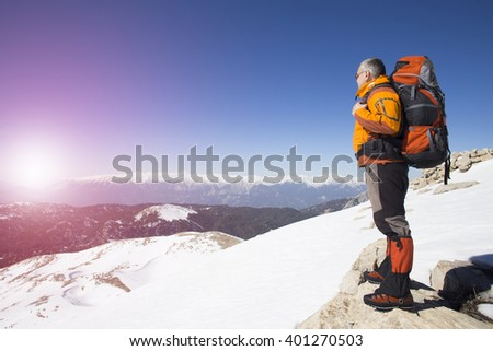 A traveler stands on top of a mountain and watching the sunrise. - stock photo