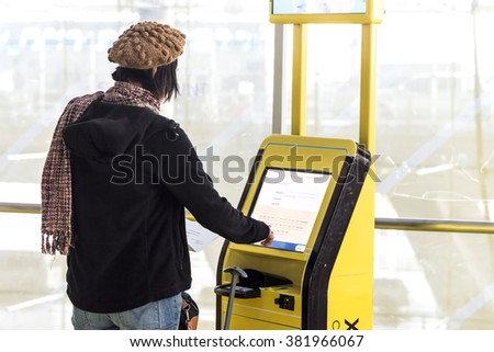a traveller using self service check in machine at airport - stock photo