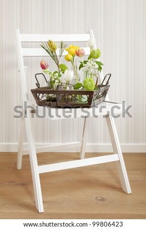 A tray full of different flowers on a folding chair - stock photo