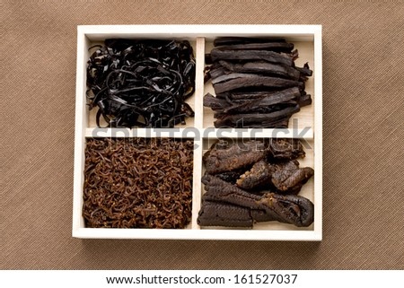 A tray with four compartments filled with food samples. - stock photo