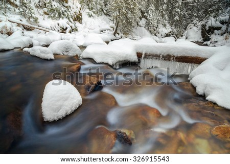 a tree bridge in snow with icicles over the river, russian nature - stock photo