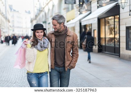 A trendy couple is walking arm in arm in the city center. They are in a cobbled car-free street. The woman is wearing a black hat and a pink shopping bag and the grey hair man has a leather coat - stock photo