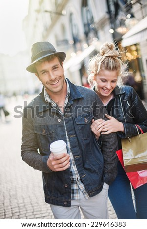 a trendy young couple walks in the city in autumn, the young woman wears a leather jacket , shopping bags at her arm and the man a cup of coffee in hand - stock photo
