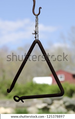 A triangle used as a dinner bell at a Connecticut farmhouse - stock photo