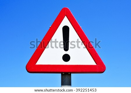 a triangular traffic sign with an exclamation mark against the blue sky - stock photo