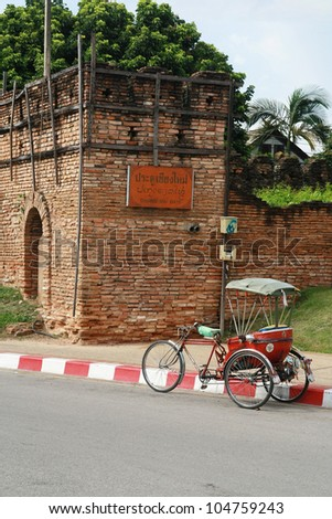a tricycle and antique Chiang Mai city wall, Thailand - stock photo