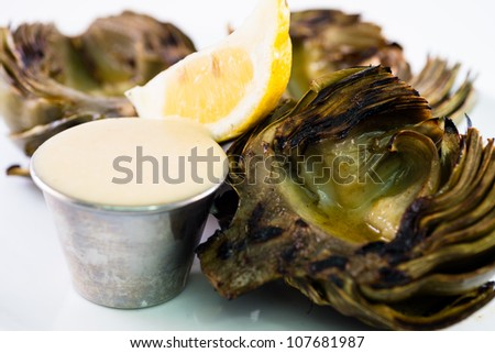 A  trio of barbequed artichoke halves sit on a white plate with a lemon and dipping sauce. - stock photo
