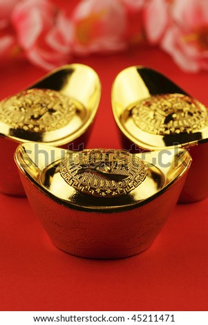 A trio of chinese gold ingots on a red background with some cherry blossoms in the background - stock photo