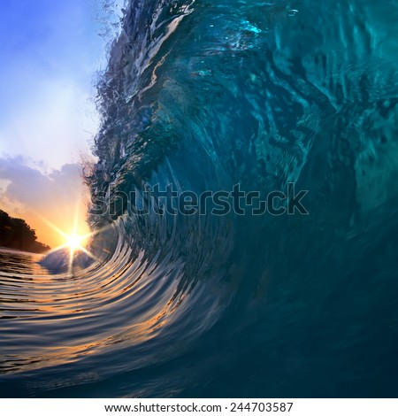 A tropical beach paradise with swirling surfing wave and sunset - stock photo