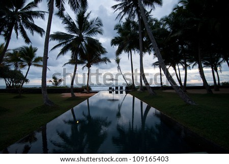 A tropical resort with a beautiful Infinity pool in the evening - stock photo