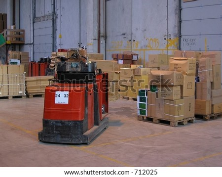 A truck and pallets in a warehouse - stock photo