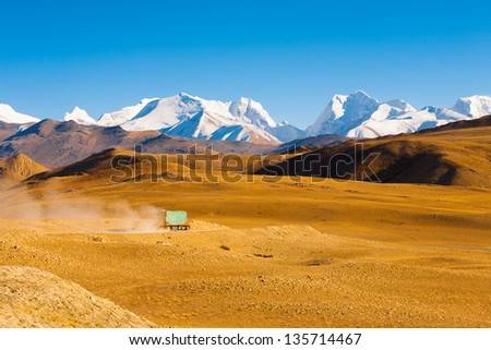 A truck drives through the barren landscape of the mountainous border between Tibet and Nepal as snowcapped himalayan mountain peaks poke through in the distance - stock photo