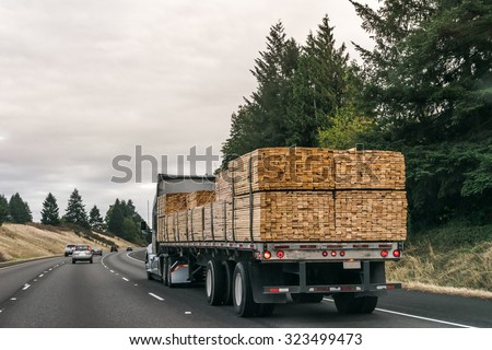 a truck  of lumbers moving on the road. - stock photo