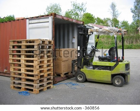A truck unloading pallet from container - stock photo