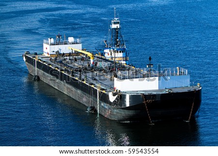 A tugboat assisting a barge isolated on the ocean - stock photo