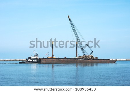 A tugboat pushes a floating crane on a barge and other repair equipment and materials toward the breakwall between the open waters of Lake Erie and the harbor at Cleveland, Ohio - stock photo
