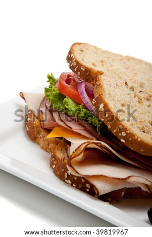A turkey sandwich with turkey, lettuce, onion, tomato and cheese on whole grain bread on a white background - stock photo