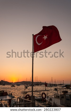 A Turkish flag flies over the port of Bodrum. in Turkey. - stock photo