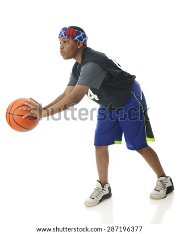 A tween African American athlete ready to pass a basketball.   On a white background. - stock photo