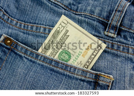 A twenty dollar bill sticking out the front pocket of denim blue jeans - stock photo