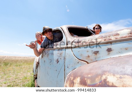 a two girls and guy in old rusty car - stock photo