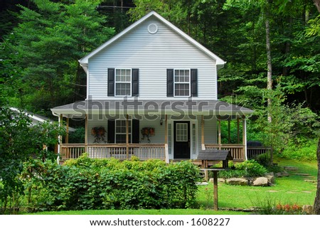A two-story farm house in the countryside surrounded by tall trees of the forest. - stock photo