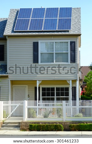 A two story residence has used available roof space to mount solar panels to defray utility company  electrical charges. - stock photo