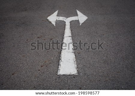 A two way arrow symbol on a black asphalt road surface. - stock photo