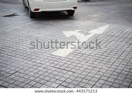 A two way white arrow symbol on a black road surface. - stock photo