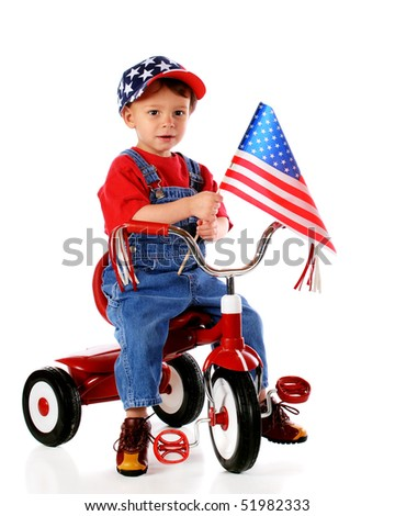 A two-year-old waving an American flag while riding a trike and wearing a stars-and-stripes baseball cap.  Isolated on white. - stock photo