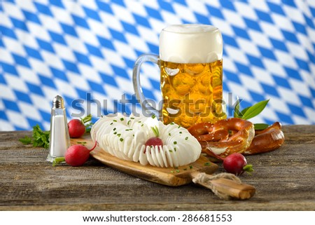 A typical Bavarian snack: Spirally cut and salted radish with pretzels and a liter of Bavarian beer on a wooden table, in the background the white-blue flag of Bavaria - stock photo