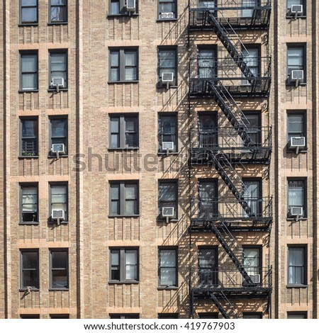 A typical brown brick apartment block found downtown in the Chelsea district of Manhattan, New York City. - stock photo