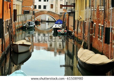 a typical canal in Venice with boats including a gondola tied up next to houses and a bridge over the waterway - stock photo