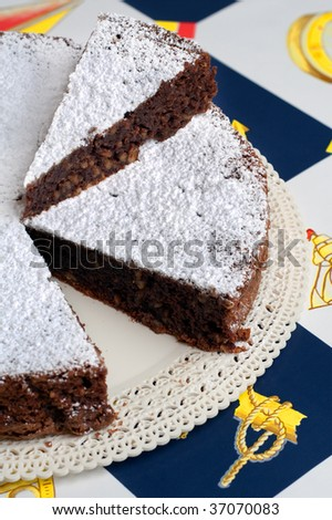 A typical italian cake torta caprese made of chocolate and almonds with a slice placed over the cake - stock photo